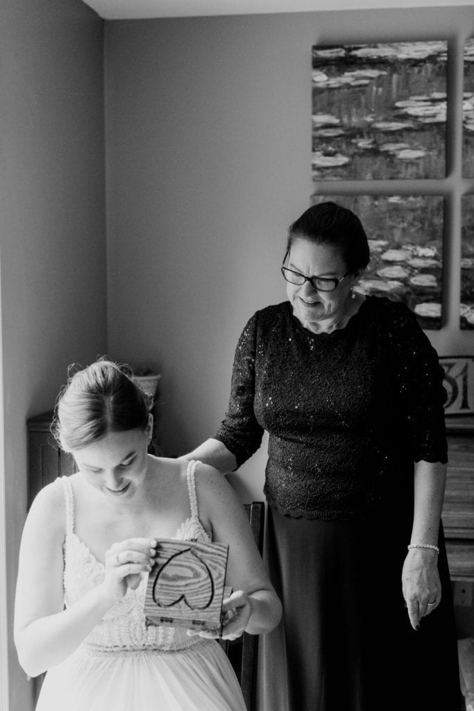 black and white photo of bride showing surprise while opening a wooden box with a heart carved into it with family member standing behind her