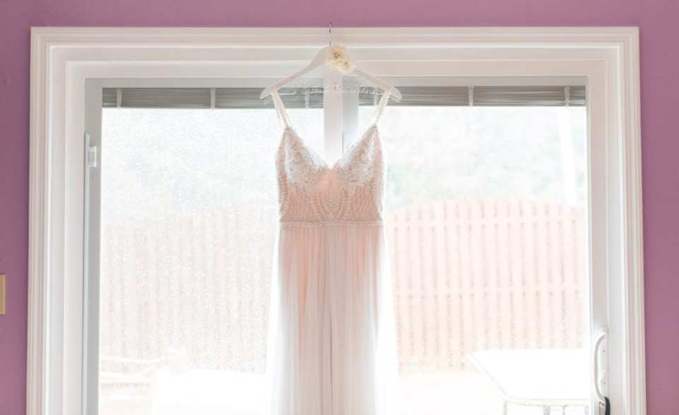 bridal gown hung on personalized wooden and wire hanger against a large window