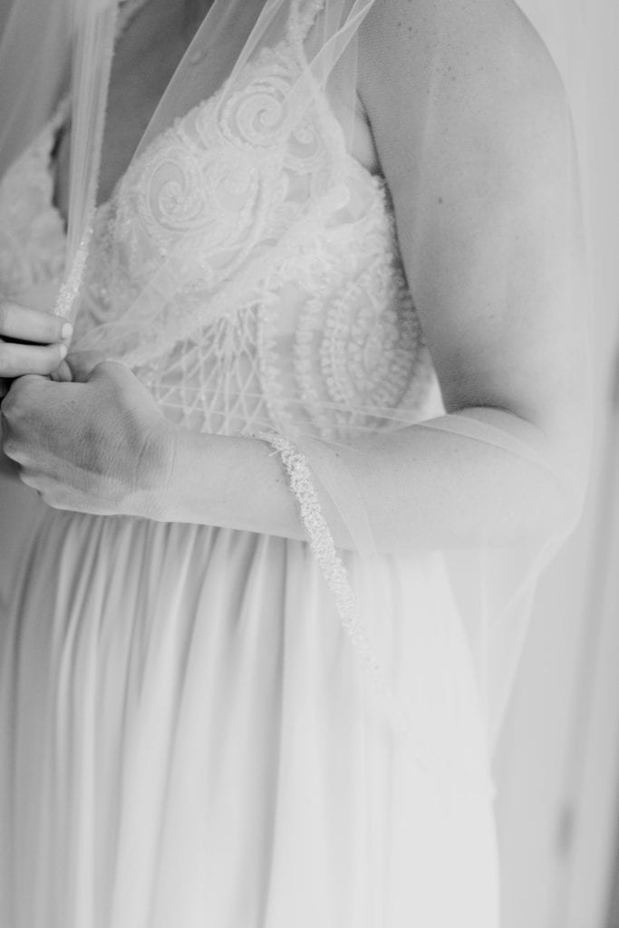 3/4 black and white shot of the bride in her gown with her veil wrapped around her