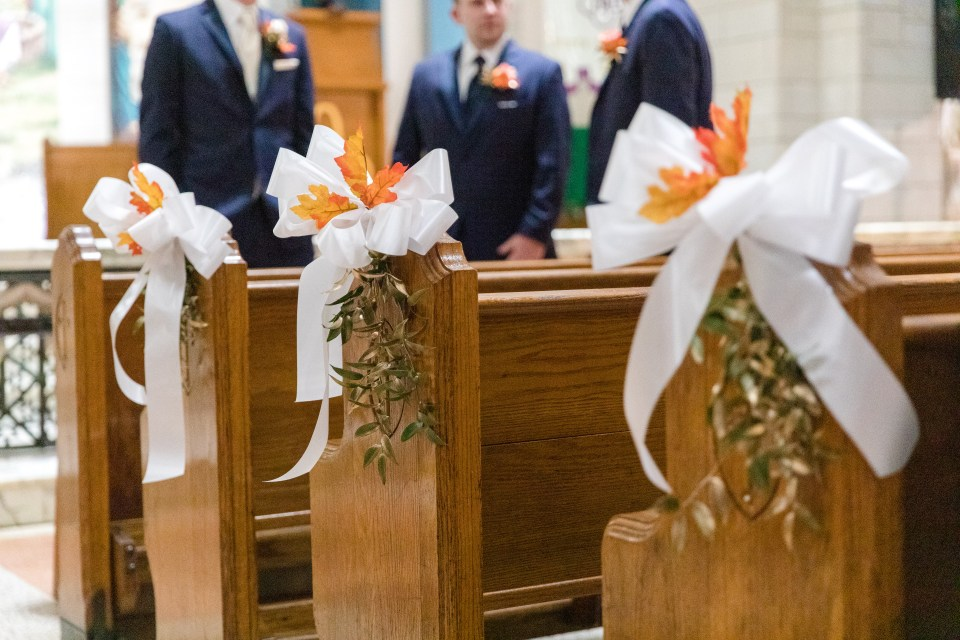 church pews decorated with fall leaves, white bows and hanging vines