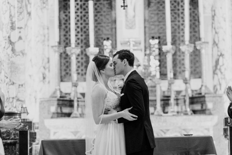 black and white photo of bride and groom kissing for the first time as mr and mrs