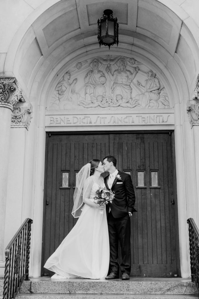 black and white photo of bride and groom kissing outside the church doors
