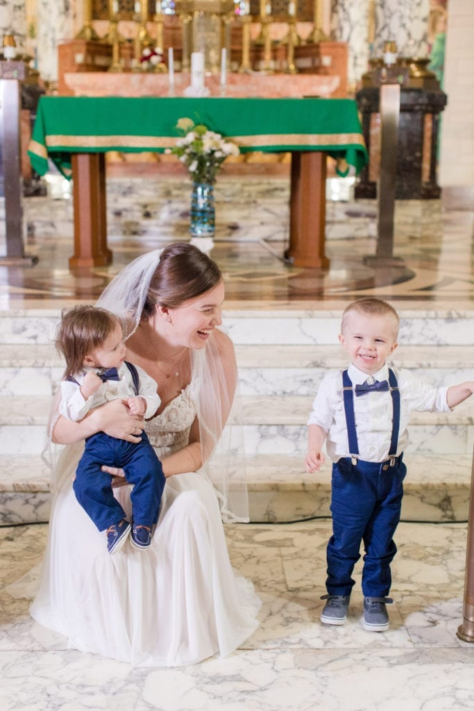 candid photo of bride laughing with two small ringbearers