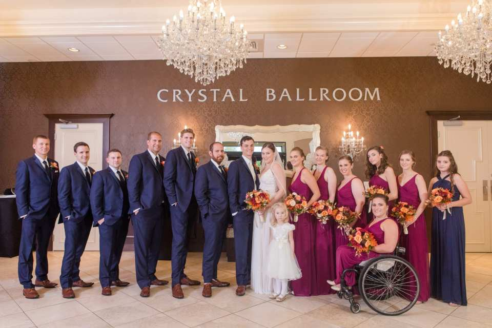 formal wedding party photo with groomsmen in navy blue suits and bridal party in raspberry gowns underneat the crystal ballroom signage