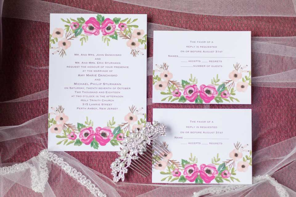 white invitation suite with dark and light pink flowers on the edge displayed on the brides veil with bridal accessories
