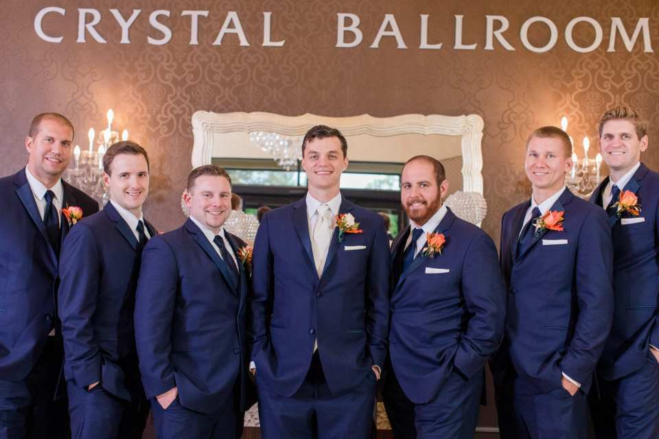formal portrait of groom with groomsman underneath the Crystal Ballroom sign