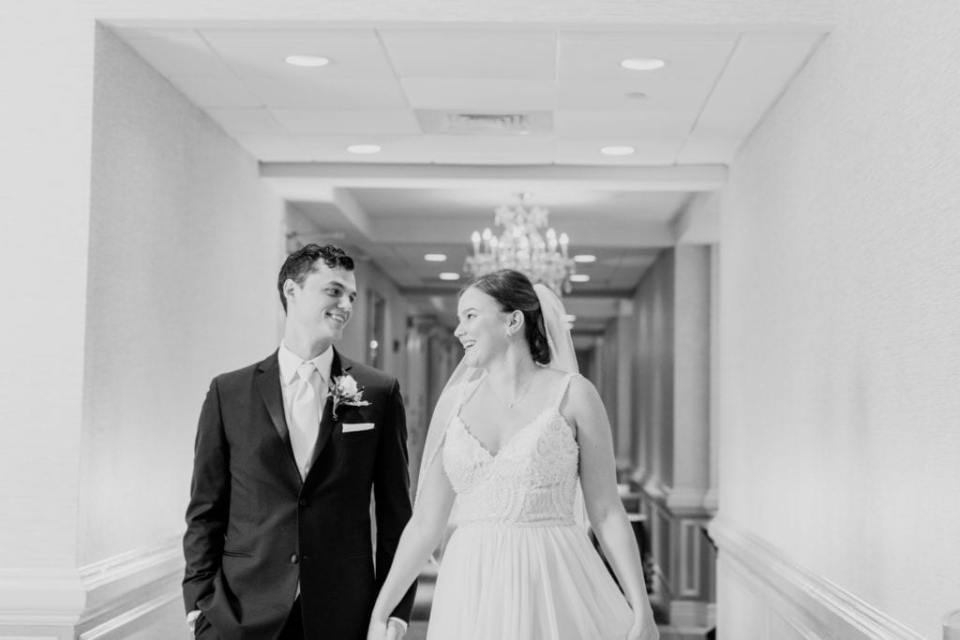 black and white photo of bride and groom gazing into one anothers eyes walking down the hall