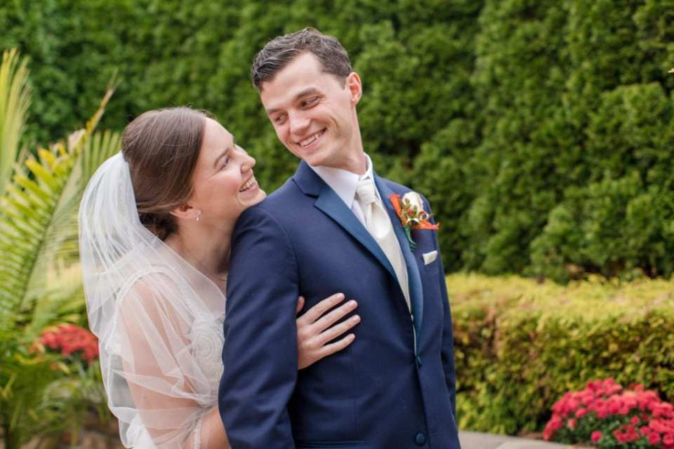 close up of the bride and groom portrait smiling at each other outdoors
