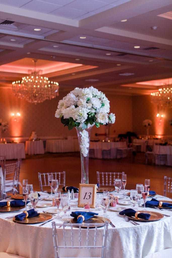 reception table with tall white floral arrangement on clear vase on top of white table linens, and multiple place settings consisting of gold chargers, navy blue napkins, gold napkin rings and clear lucite chivari chairs