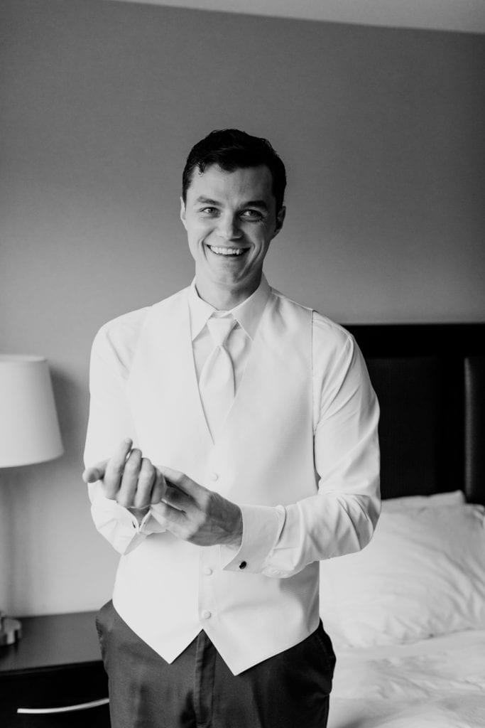 black and white candid photo of groom putting on his cuff links