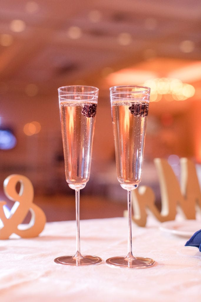 two filled champagne glasses with berries on sweetheart table in front of Mr and Mrs sign