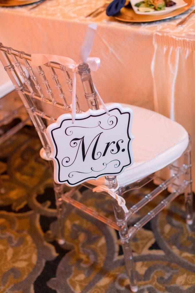 White 'Mrs.' sign hanging from a lucite chivari chair