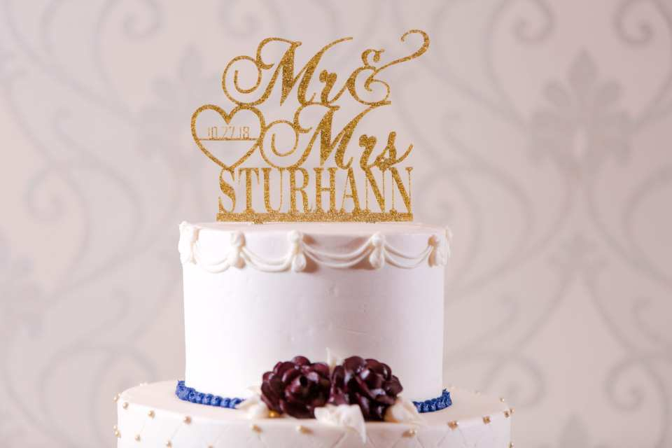 close up photo of top tier of wedding cake with gold glitter Mr and Mrs cake topper