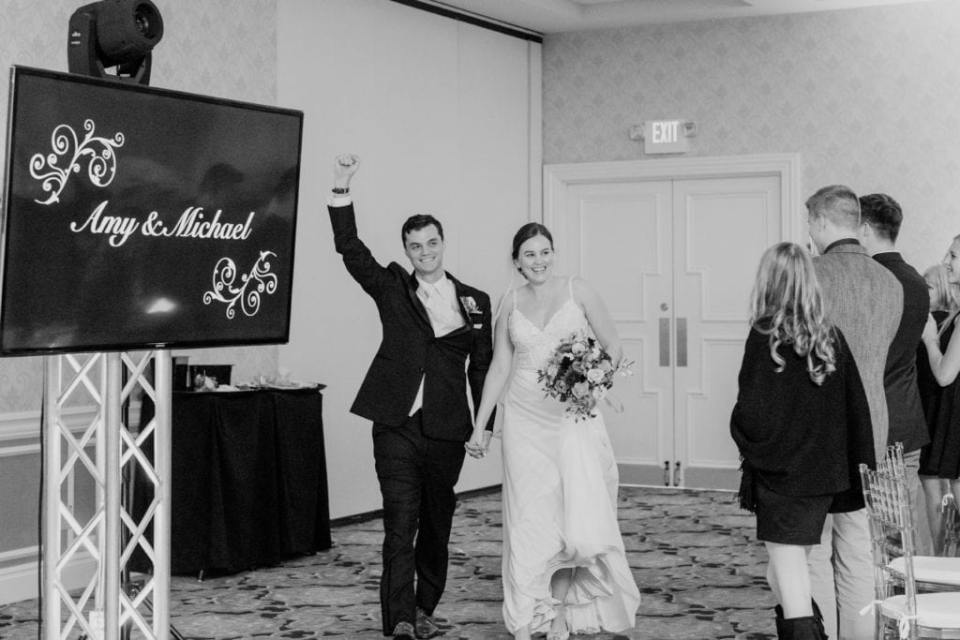 black and white photo of bride and groom making their entrance into the wedding reception