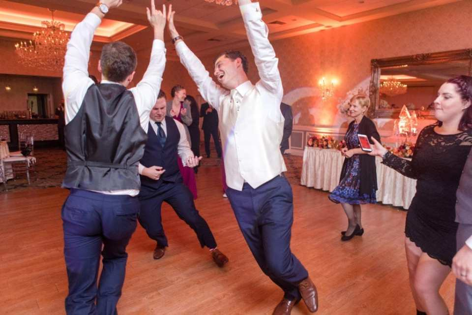 groom dances during reception with groomsmen while other guests look on