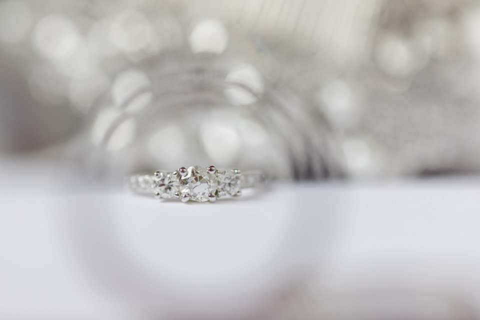 three stone diamond ring with channel set diamonds on band  displayed on white