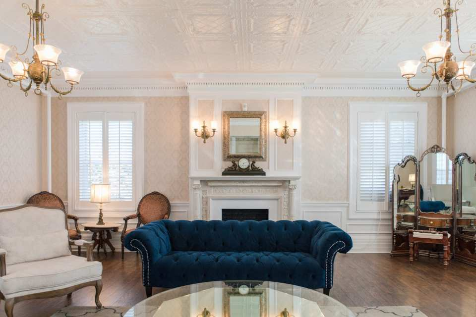 Bridal suite at Shadowbrook at Shrewsbury with navy blue tufted sofa in center in front of fireplace, antique mirrored vanity in corner