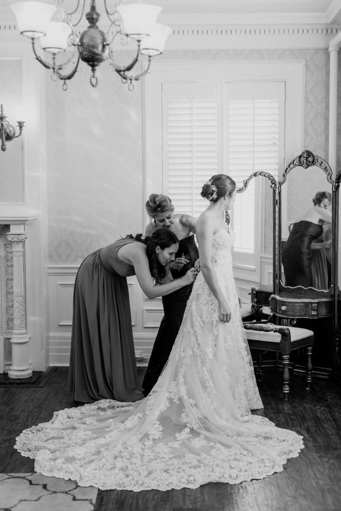 black and white photo of bride being helped into her gown by her mother and member of the bridal party in front of the antique makeup vanity