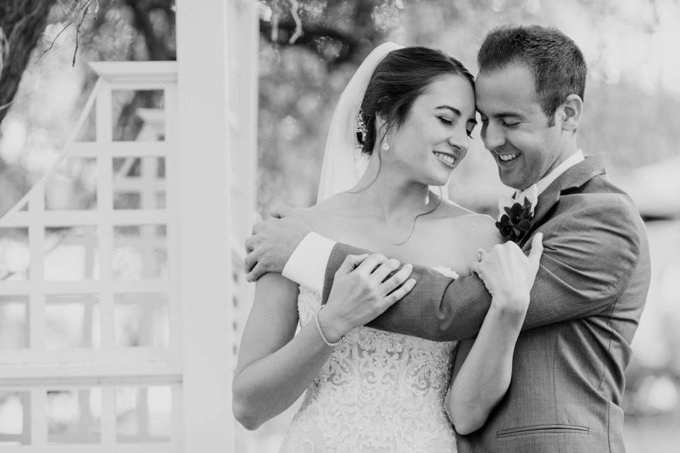 black and white photo of groom holding bride by trellis in gardens