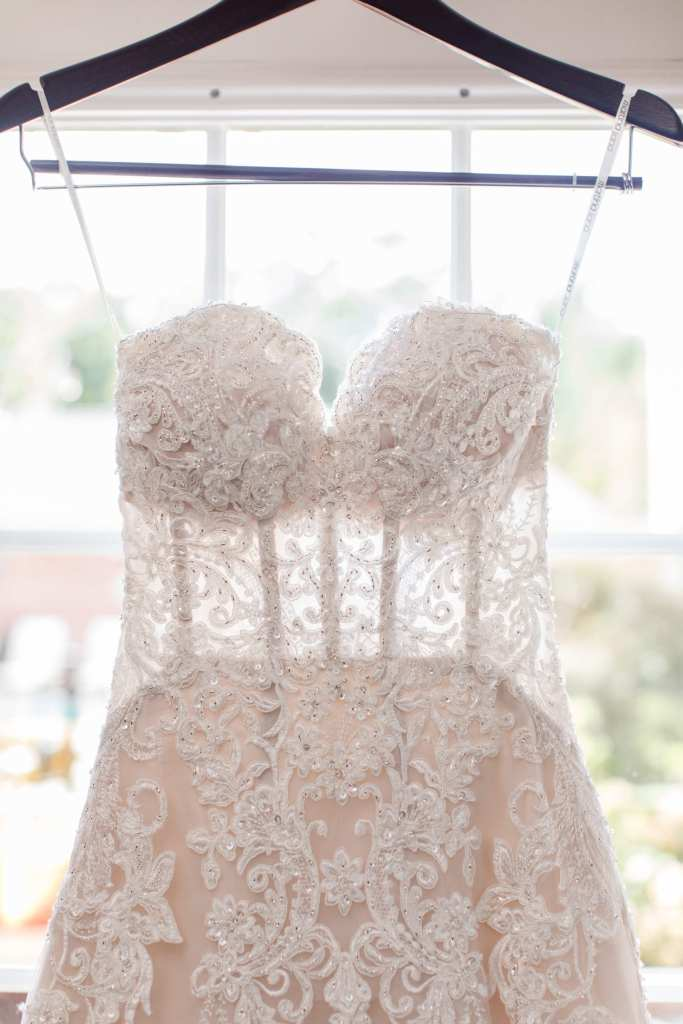 applique bridal gown hanging in front of window on display