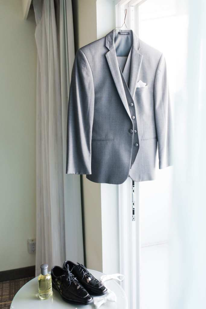 grooms gray tuxedo jacket hanging on display in front of window with tuxedo shoes and cologne and bow tie