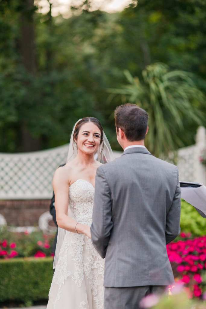a photo of the bride smiling as she and her groom take part in the wedding ceremony