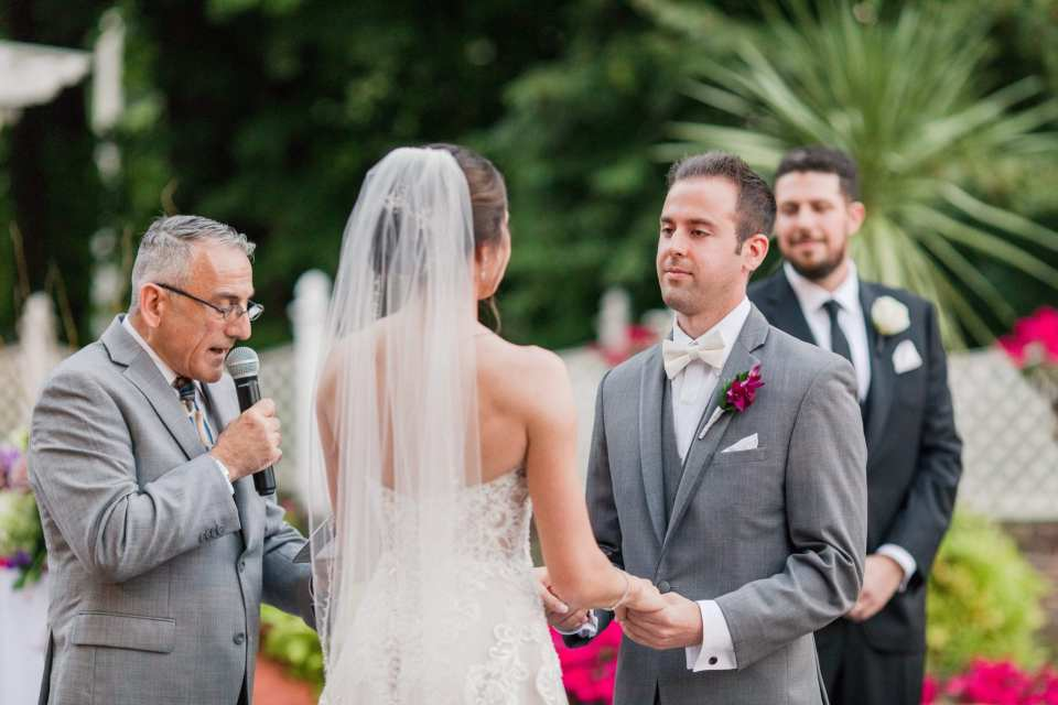 a photo of the groom listening intently as the officiant proceeds with the ceremony