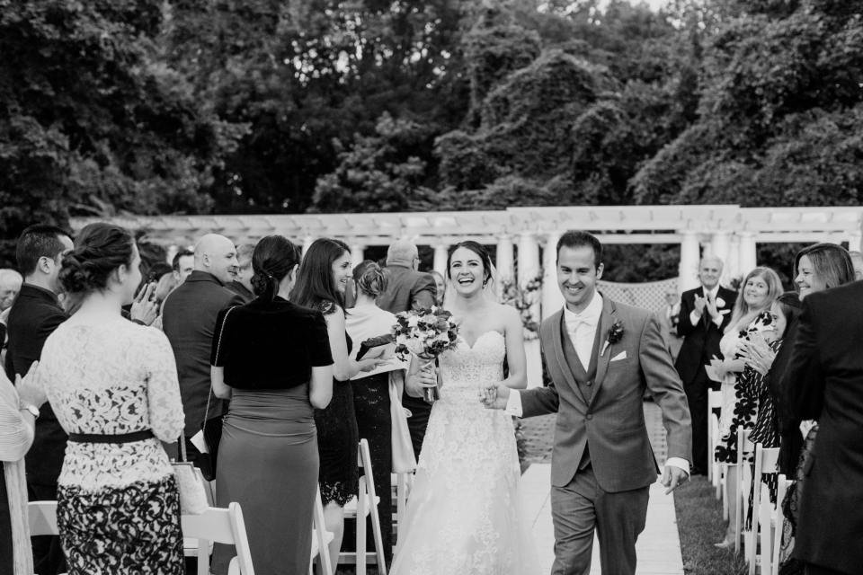 black and white photo of the bride and groom walking down the aisle after the ceremony