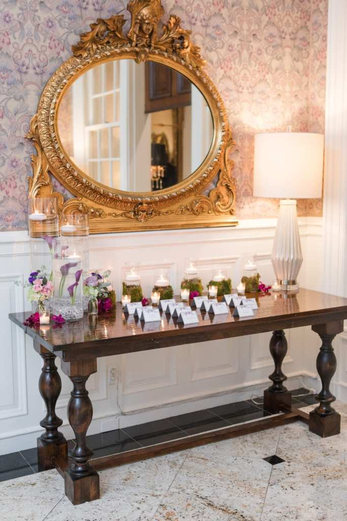 dark wood card table in front of gold mirror decorated with candles, cylindrical vases filled with water, candles and lilies