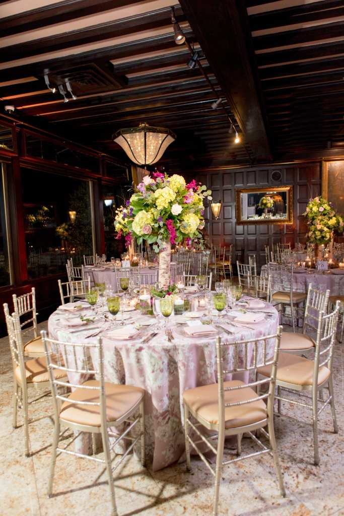shot of reception table with floral print linens, off white chivari chairs, green glassware, and tall table arrangement with birch wood stalk topped with greenery, lavender and cream roses, pale green hydrangeas, fuschia orchids