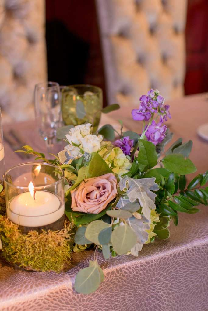 close up shot of florals on the sweetheart table consisting of a dusty rose roses, hyrdrange, eucalyptus, misc greenery and a moss wrapped candle