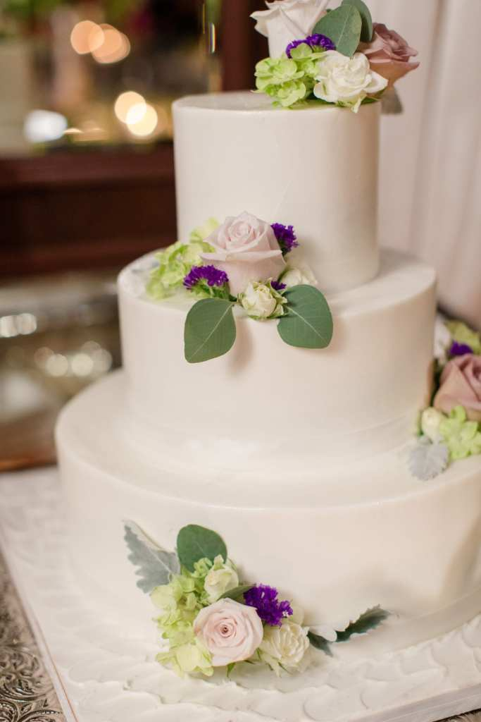 three tier simple smooth white cake adorned with coordinating roses in blush with purple accent flowers and greenery
