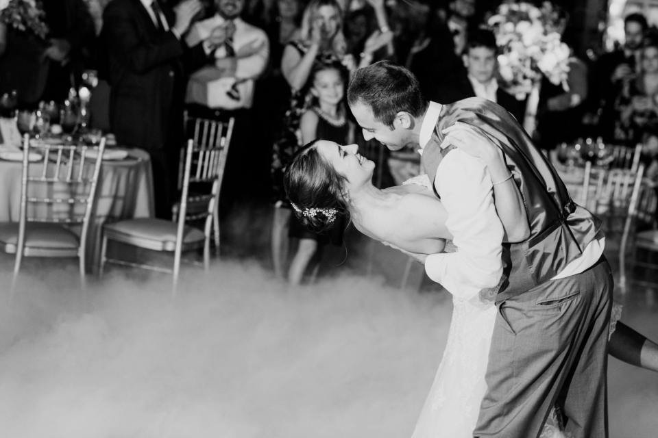 black and white photo of bride and groom taking a dip during their first dance surrounded by smoke