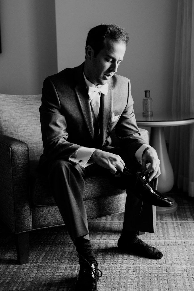 black and white candid photo of groom sitting down while putting on his shoes