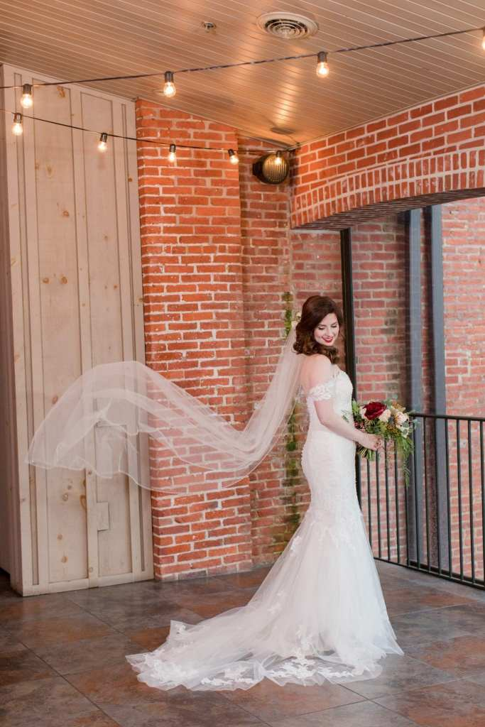 bridal portrait with brides veil in air under cafe lights