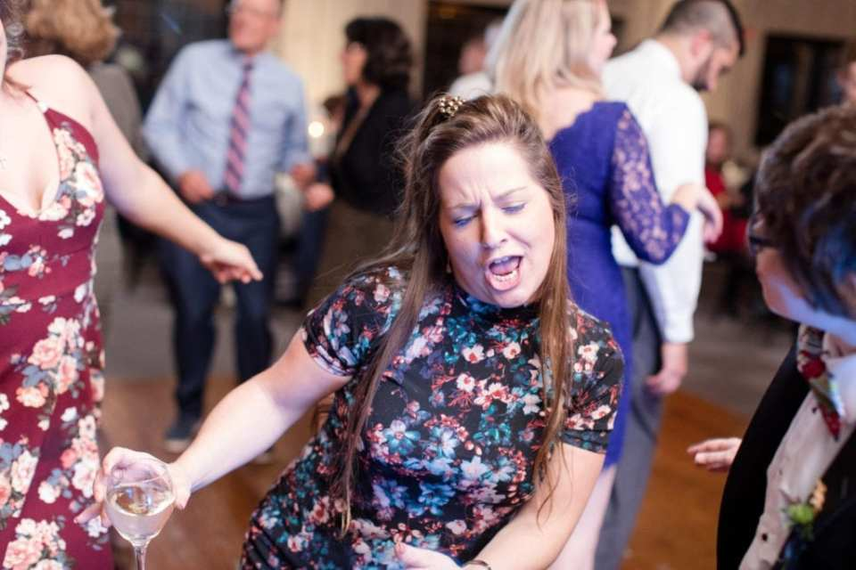 female guest in floral print dress dancing during reception