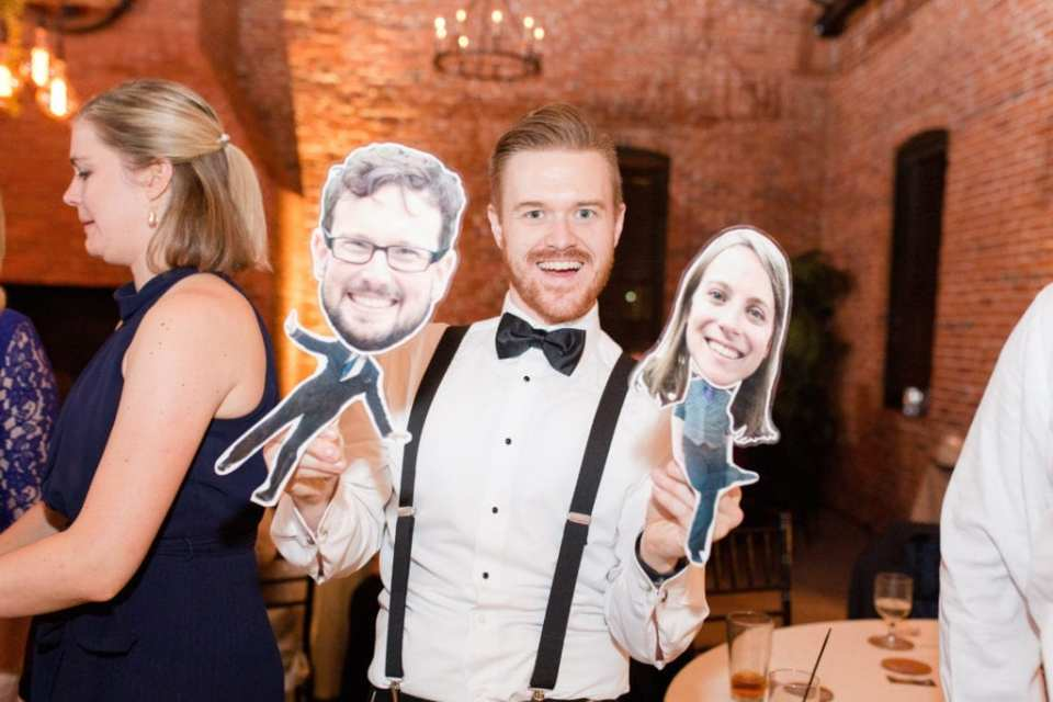 male wedding guest in suspenders and bow tie holding paper dolls of friends