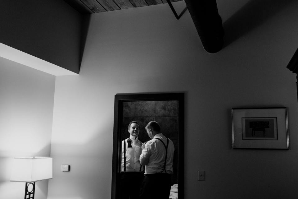 black and white photo of groom being assisted with his bow tie by a member of the wedding party