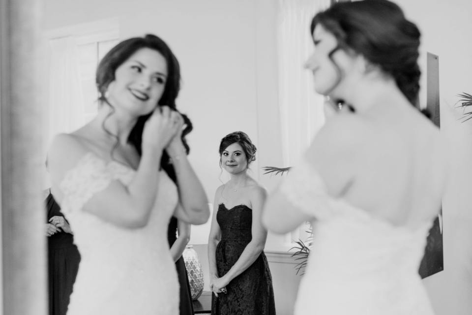black and white photo of bride putting in her earring while looking at herself in the mirror with bridal party looking on