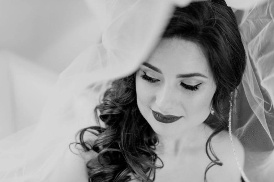 black and white photo of bride under veil looking down
