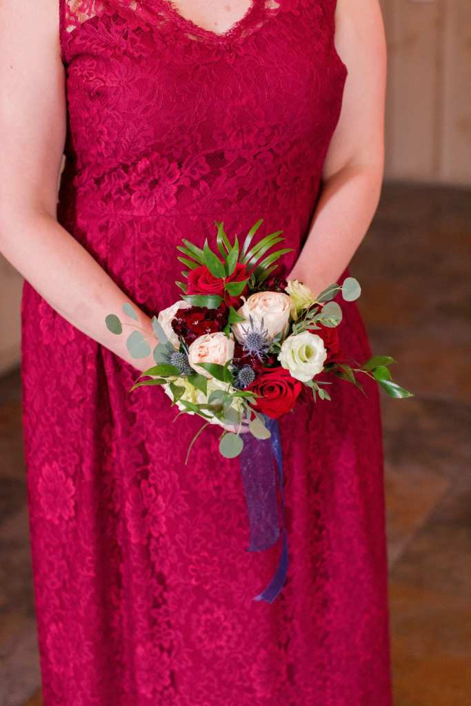 close up of bridal party bouquet of white, pink and blush roses wrapped in navy chiffon ribbon in front of red lace bridesmaids gown