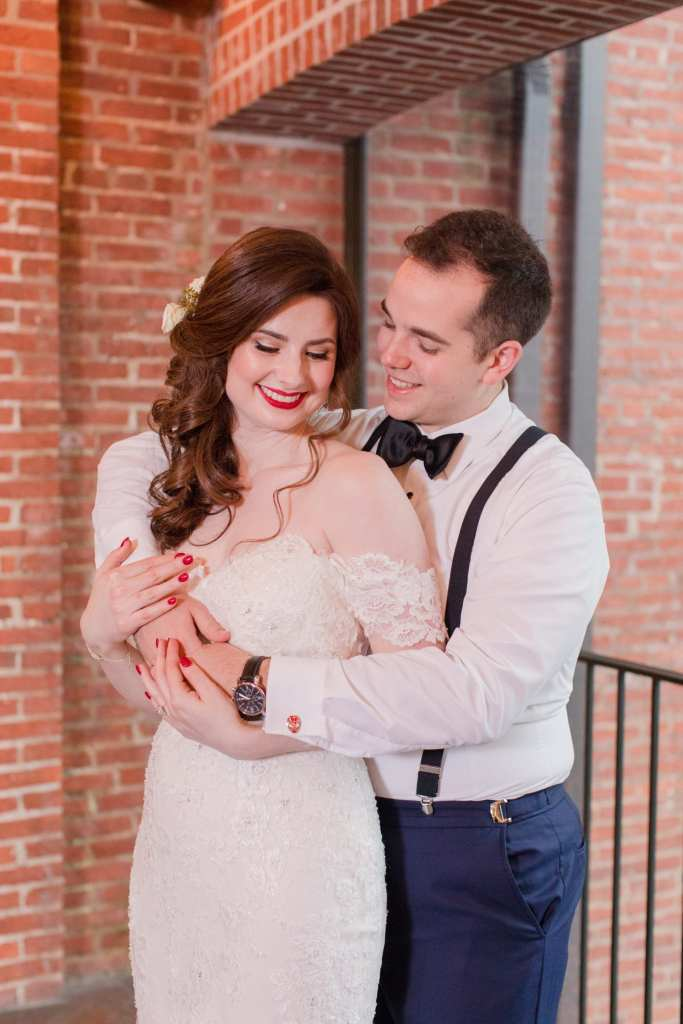 bride wrapped up in grooms arms in sweet smiling photo