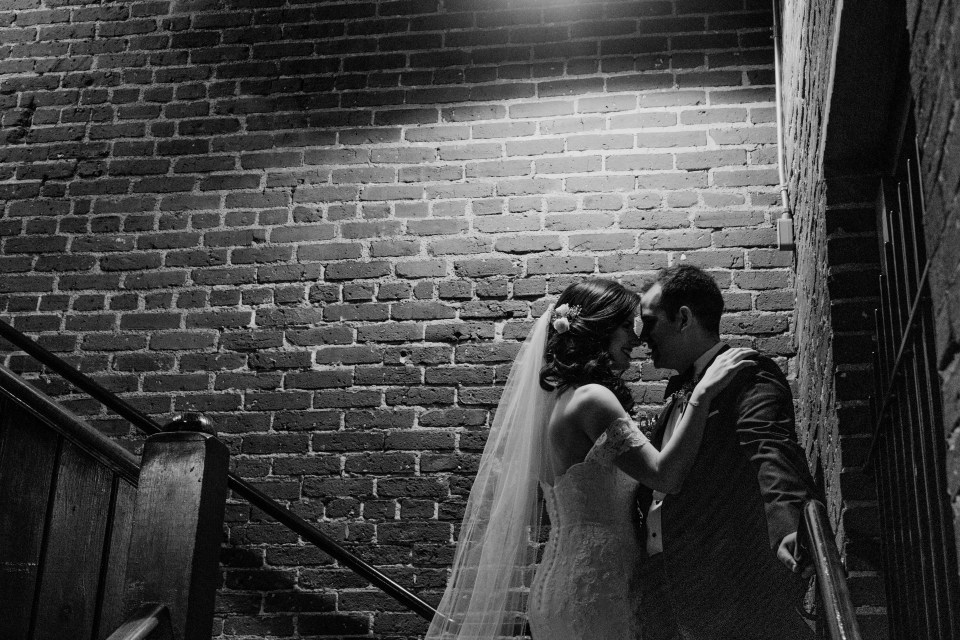black and white candid photo of bride and groom looking at each other lovingingly inside the hotel under a dim light