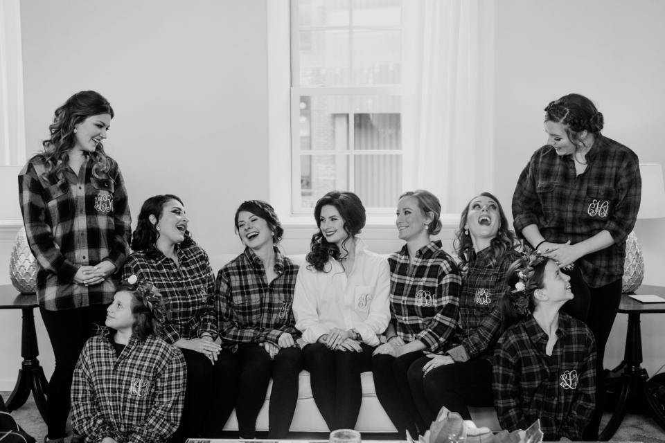 black and white photo of bride with her bridal party in coordinating monogrammed flannel shirts