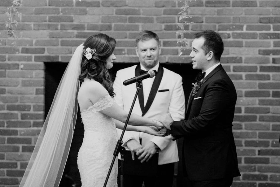 black and white photo of bride and groom taking their vows in front of brick walled fireplace and officiant in white tuxedo jacket