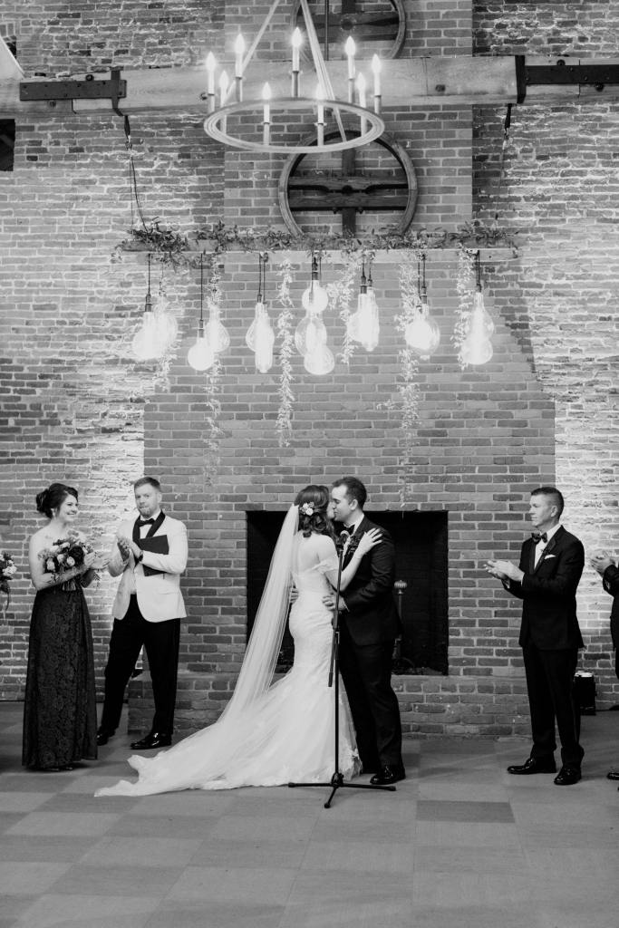 black and white photo of bride and groom's first kiss as husband and wife in front of brick walled fireplace with hanging florals and lights
