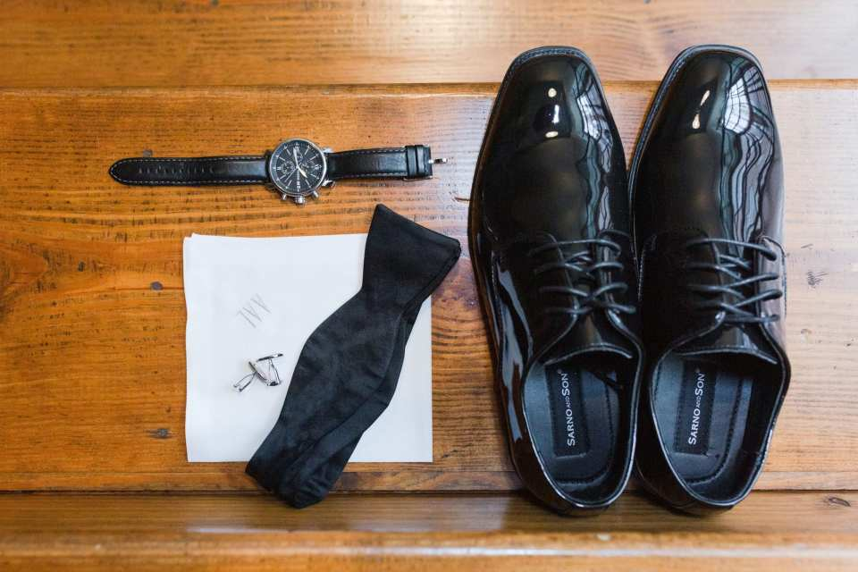 grooms accessories of shoes, bow tie, cuff links, black watch and embroidered handkerchief