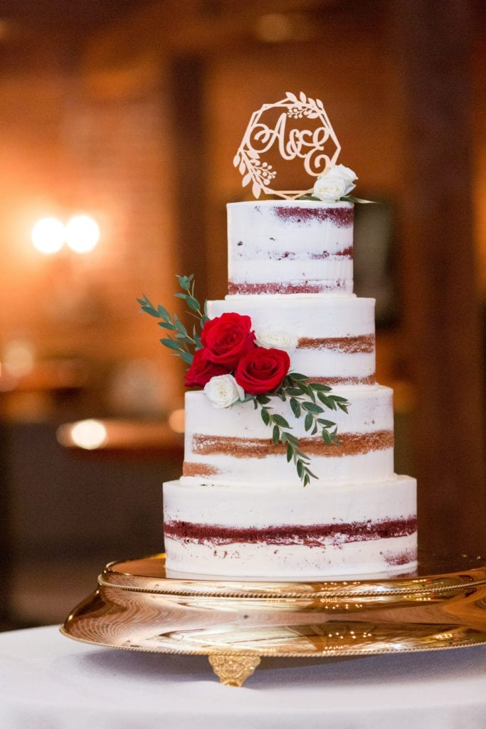 4 tier semi naked wedding cake with red and white rose accents and monogram initial cake topper