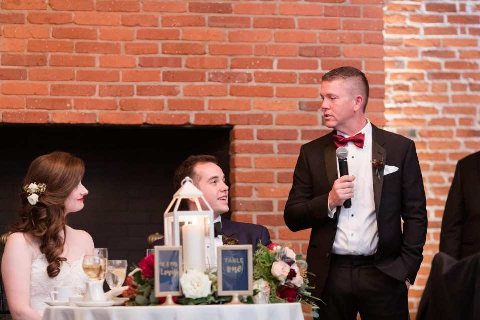 best man in black tuxedo with red bow tie giving speech during toasts