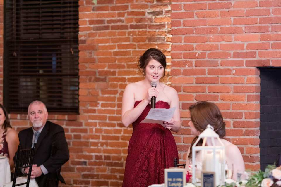 maid of honor in red gown giving speech during toasts